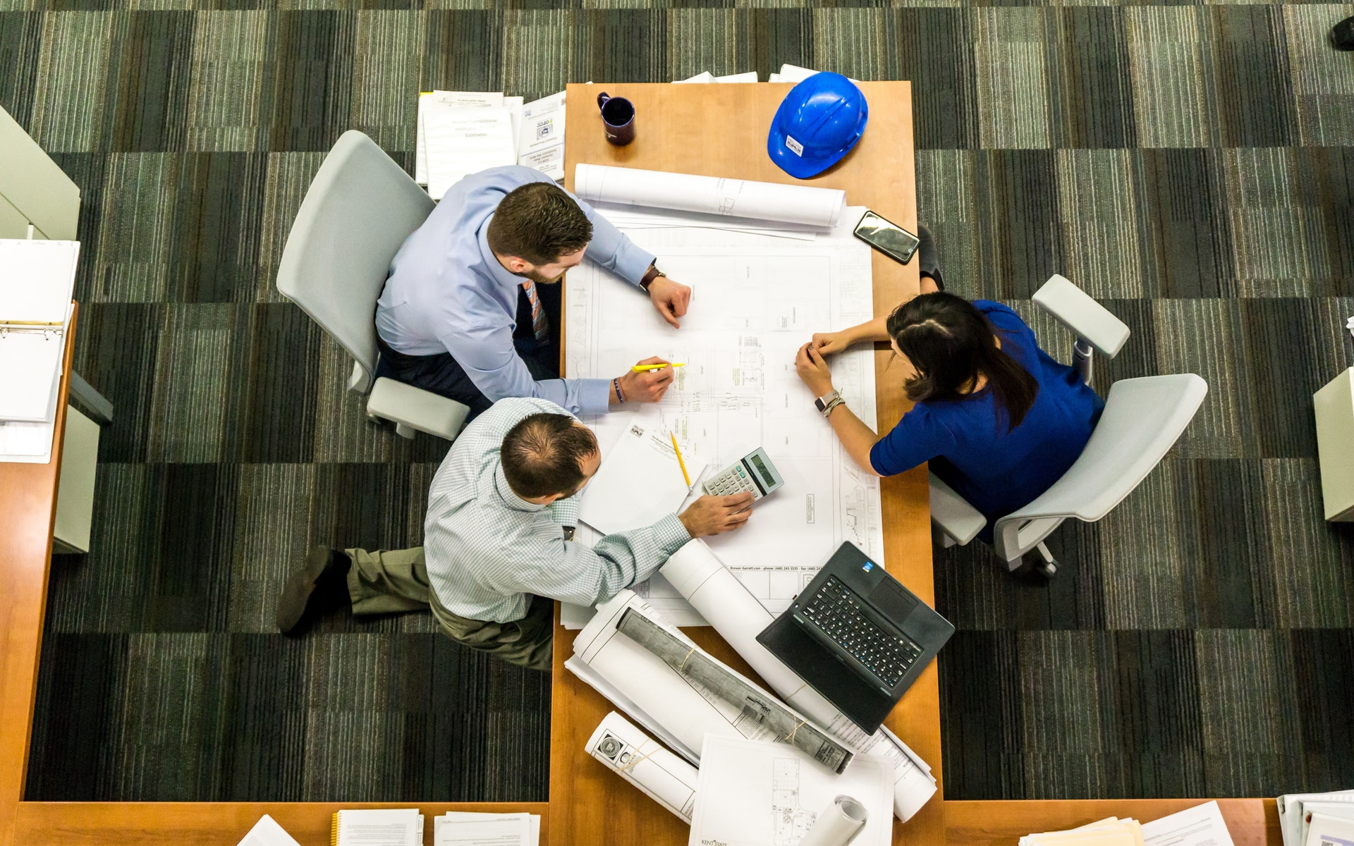 Workers huddle around table with plan sketch.
