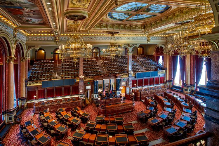 Interior of the Iowa state legislature - desks and dark wood with a gilded ceiling