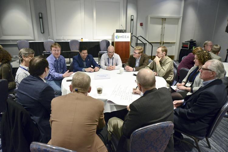 workshop attendees chat seated around a circular table