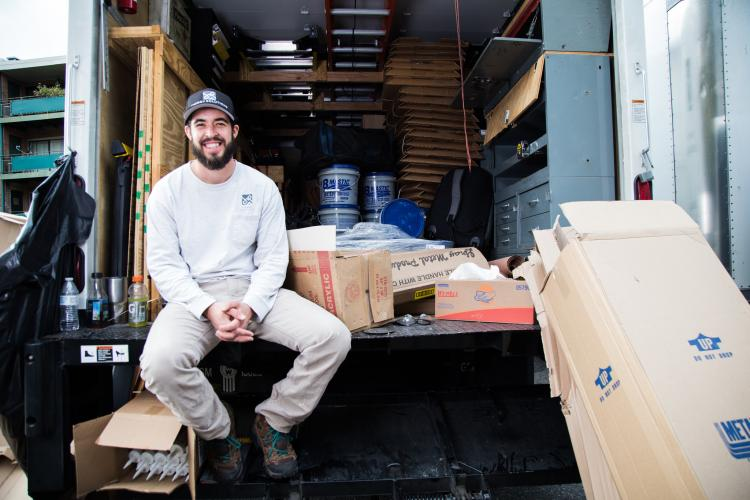 A weatherization worker smiles sitting in the back of a boxtruck.