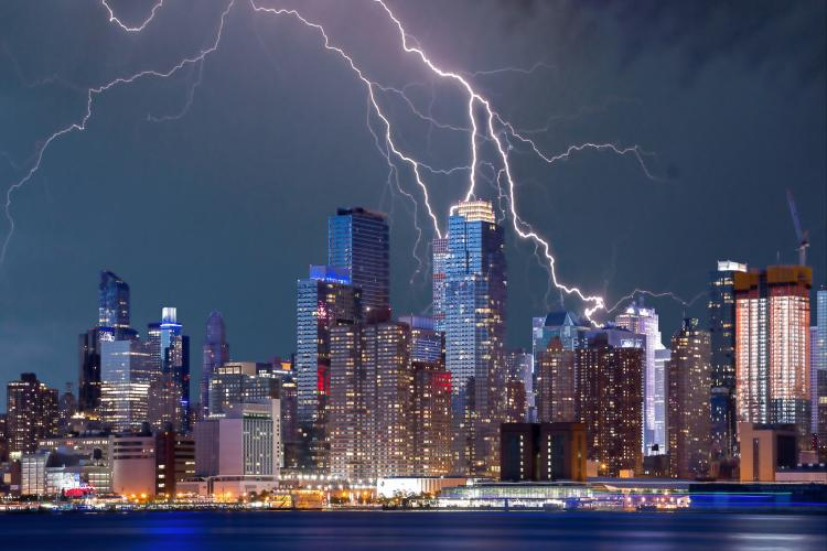 a city skyline with lighting strikes overhead