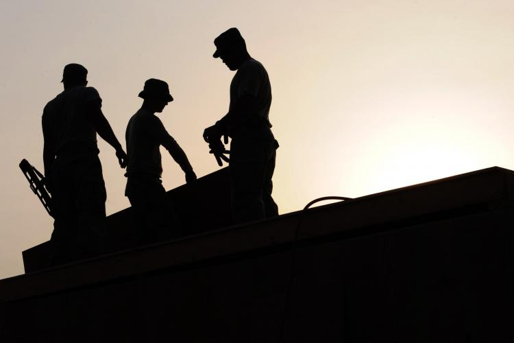 silhouette of workers on roof