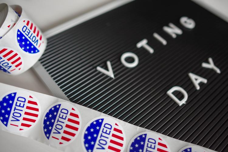 """I voted"" stickers and a sign that says ""voting day"""