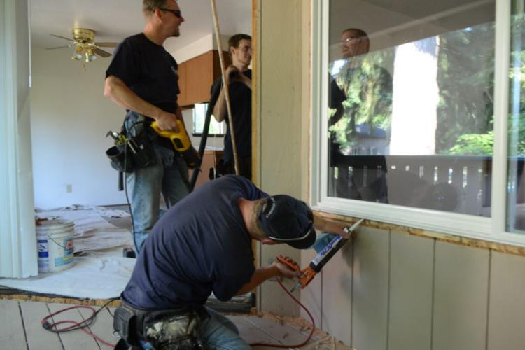 workers caulking spaces around windows