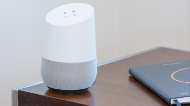 a google home smart speaker on a side table next to a planner
